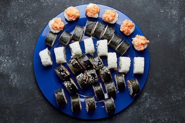 Набор для суши, на синей тарелке, на темном Premium Фотографии