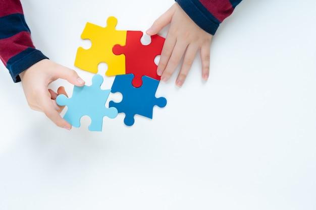 自閉症スペクトラム障害の市民の意識のカラーパズルシンボルを配置する小さな子供の平面図手。世界自閉症啓発デー、思いやり、発言、キャンペーン、連帯。分離されました。 Premium写真