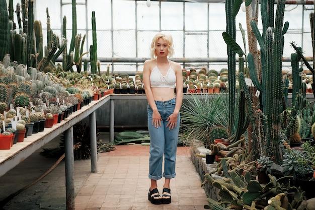 Красивая блондинка позирует в тропическом ботаническом саду Premium Фотографии