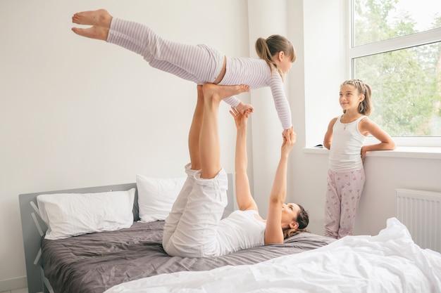 Мать с детьми делает упражнения йоги в постели Premium Фотографии