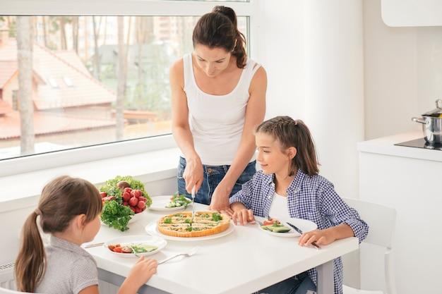 Мать готовит здоровую еду для детей Premium Фотографии