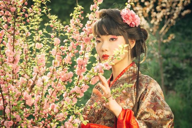 Красивая азиатская женщина в цветении сакуры Premium Фотографии