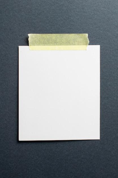 ソフトシャドウと黒のクラフトペーパーの背景に黄色のスコッチテープの空白のフォトフレーム 無料写真