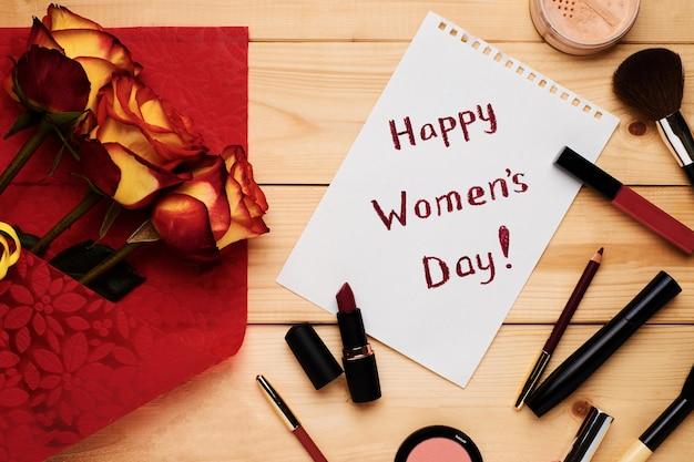 幸せな女性の日フラットはバラ、カード、化粧品、化粧品で横たわっていた。 Premium写真