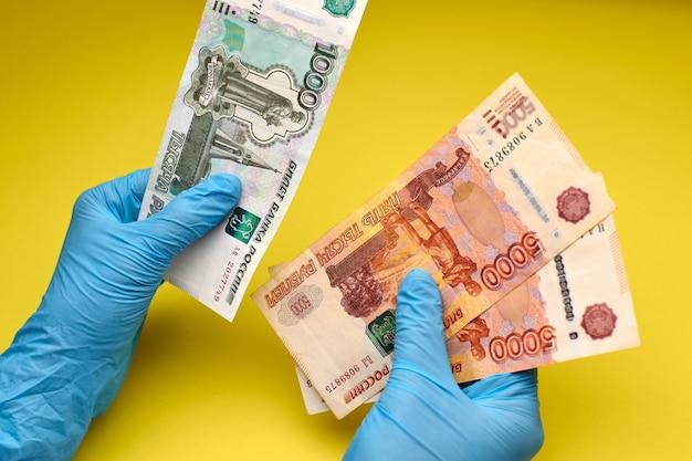 Руки в перчатках держат банкноты Premium Фотографии
