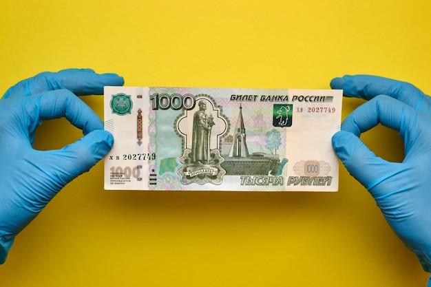 Руки в перчатках держат банкноту Premium Фотографии