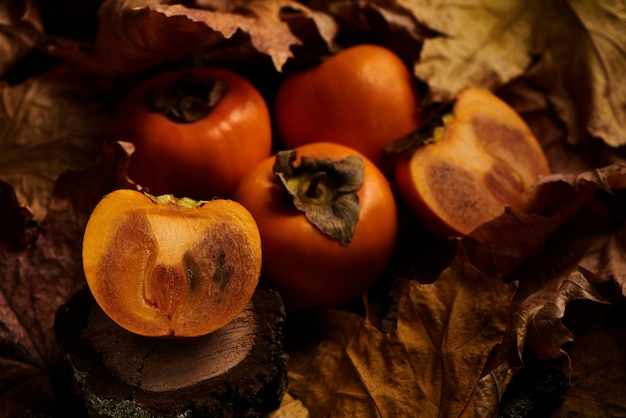 木の上のオレンジ色の紅葉の新鮮なスライスした柿果物 Premium写真