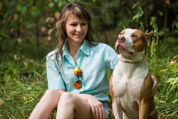 Веселая дама сидит на траве с собакой питбуль. Premium Фотографии