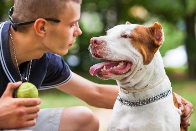 Красивый парень, играя с собакой на открытом воздухе. Premium Фотографии
