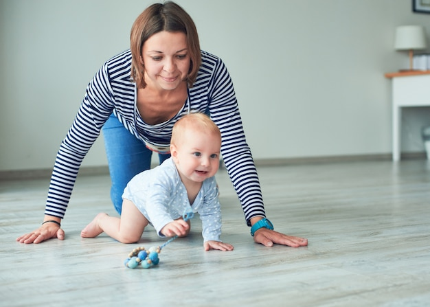 Милый ребенок и молодая мама ползут по дому Premium Фотографии