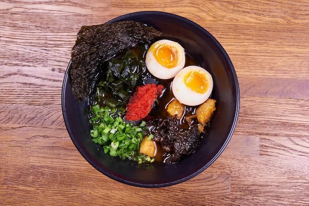Традиционный японский суп из рамена, лапша, нарезанная курица, яйца. закройте Premium Фотографии