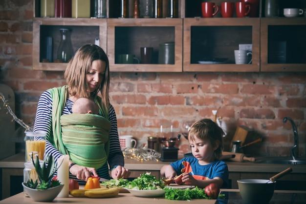 Счастливая молодая семья, красивая мать с двумя детьми, прелестный мальчик дошкольного возраста и ребенок в слинге, вместе готовить в солнечной кухне. Premium Фотографии