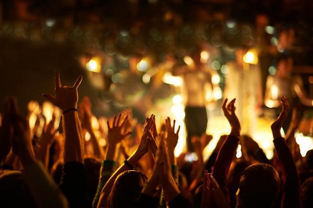 Аудитория с поднятыми руками на музыкальном фестивале и огнями, стекающими сверху над сценой. Premium Фотографии