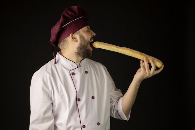 制服を着たハンサムなひげを生やしたシェフ男バゲット、男性のパン屋料理人 Premium写真