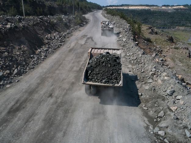 石の採石場に巨大な産業用ダンプトラックがドローンのトップショットから輸送された大理石または花崗岩を輸送 Premium写真