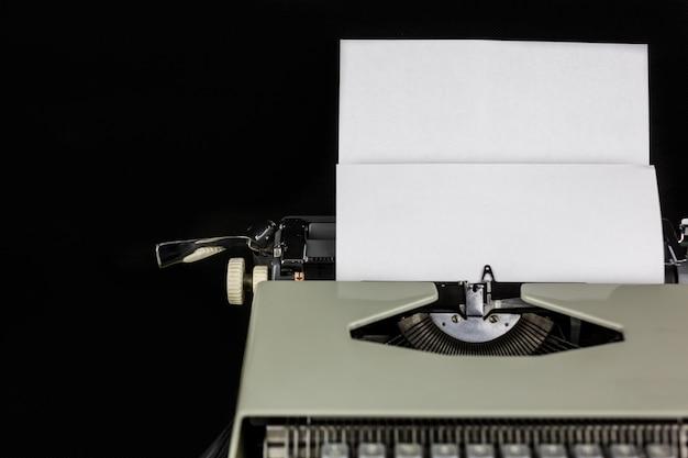 空のスペースで白い紙で黒い壁にテーブルの上のタイプライター。作家または著者の職場。新しい生活のコンセプト。 Premium写真