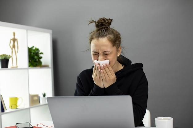 ホームオフィスのコンピューターで座っている病気の若い女性は気分が悪く、くしゃみをする Premium写真