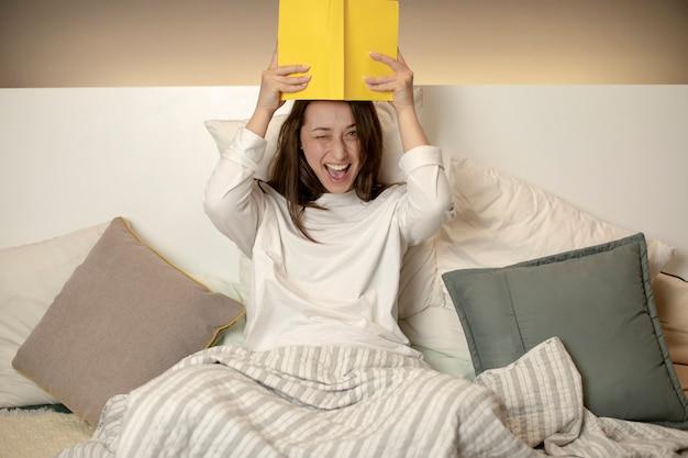 ベッドに座って、頭の上に本を持っているとふざけてウインクうれしそうな美しい女の子 Premium写真