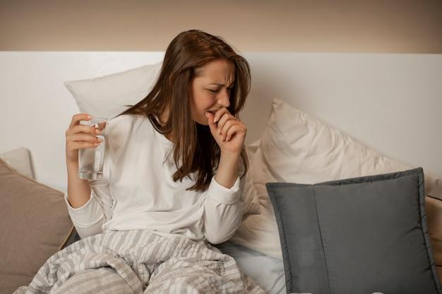 コップ一杯の水の素敵な女の子は眠ることができず、ベッドに座って気分が悪く、咳をします Premium写真
