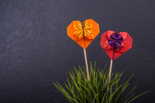バレンタインの日の愛の手作りのペーパークラフト折り紙クラフトスタジオで色紙ハートのクローズアップショット Premium写真