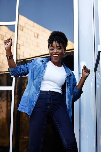 浅黒い肌のアメリカ人女性は幸せで、青い空間で踊っています Premium写真