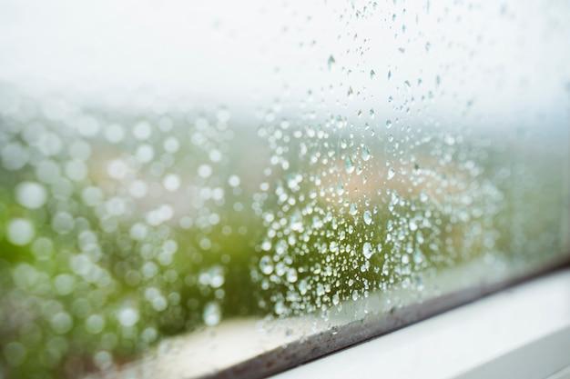雨水平背景の滴。冬の季節。家の中の湿度と雨。ウィンドウの結露。雨のウェットドロップの詳細は、自宅のきれいな窓にくっつきます。 Premium写真