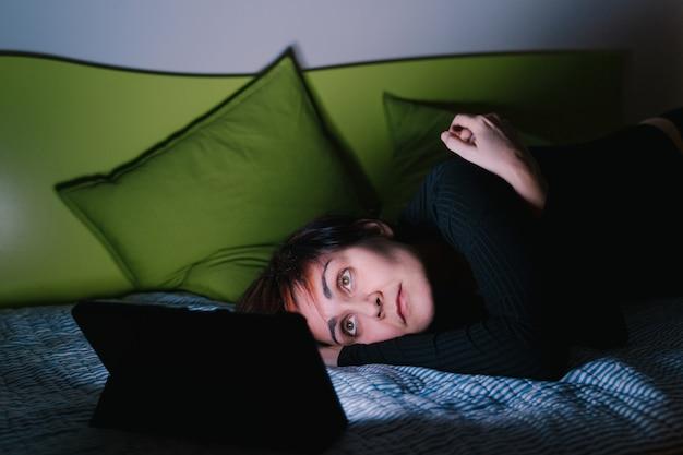ベッドでテレビを見て寝ようとしている若い白人女性。人々は寝る前に娯楽機器に接続しました。テクノロジーとレジャーのコンセプト。不眠症と不眠生活。 Premium写真