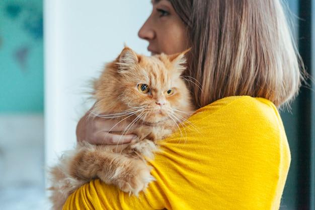 Женщина обнимает свою кошку Premium Фотографии