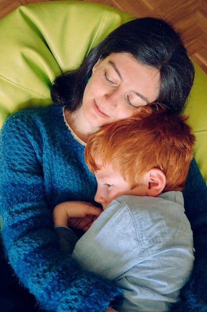 愛する母親が息子を眠らせようとする悪夢で息子を抱き締める。不眠症と不眠のコンセプトです。自宅で子供を持つ独身女性。子供がいる家の中の家族のライフスタイル。 Premium写真