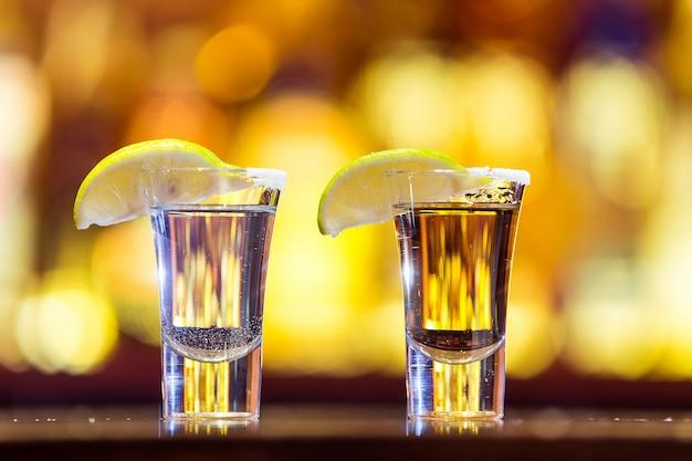明るいライトのガラスの銀と金のテキーラ。伝統的なメキシコの飲み物。 Premium写真