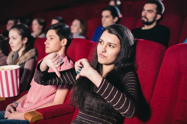 彼女が好きではない映画のセッションで映画館の女の子 Premium写真