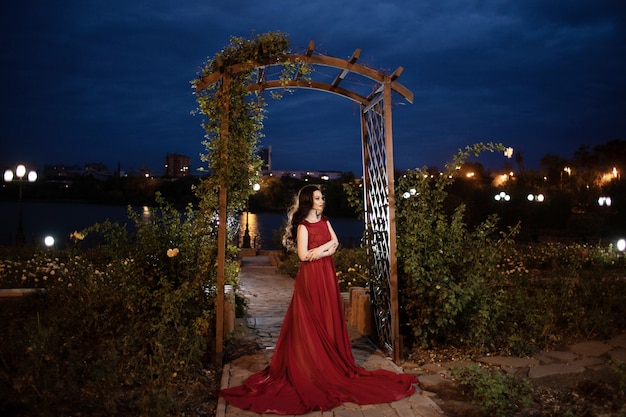 夜の公園でポーズをとる電車で赤いドレスを着た若いブルネットの女性 Premium写真