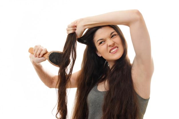 Молодая женщина не может расчесывать проблемные спутанные волосы. на белом фоне крупным планом Premium Фотографии