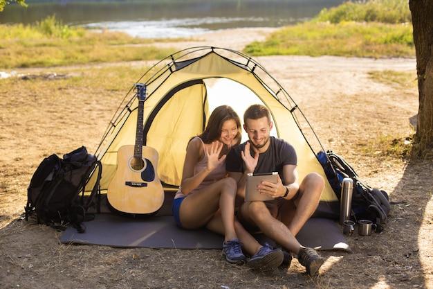 タブレットでテントの近くの男女。 Premium写真