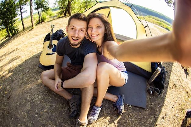 キャンプ旅行中の男女がテントの近くで自撮りをします。 Premium写真
