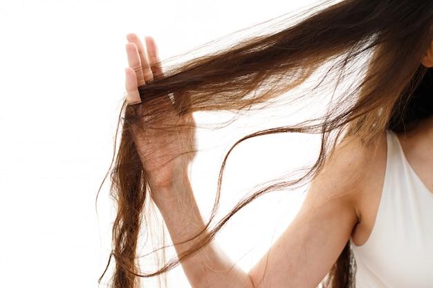 Молодая женщина с проблемными волосами. на белом изолированные Premium Фотографии