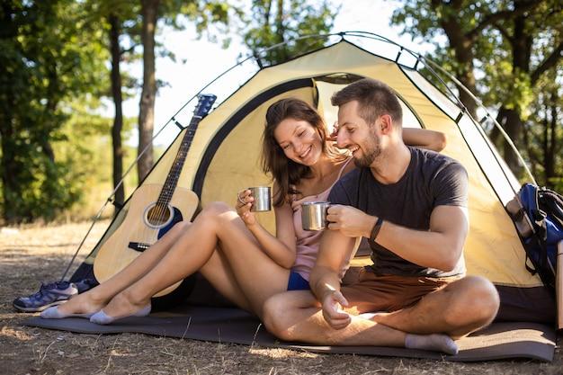 キャンプ旅行中の男女がテントのそばに座ってお茶を飲む。 Premium写真