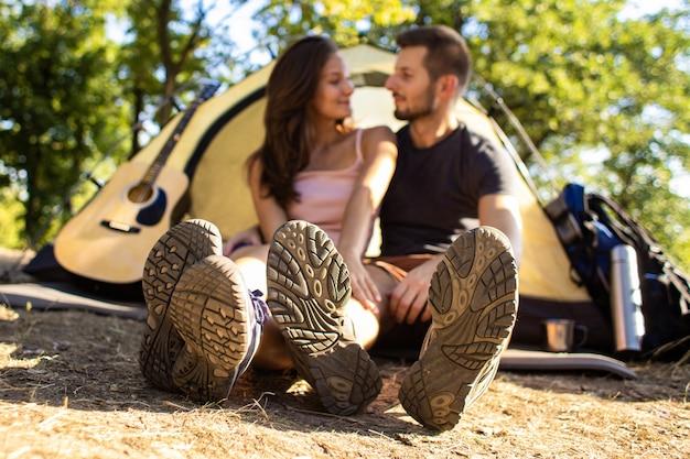 夕暮れ時のテントの近くにバックパックを持ってハイキングに出かける男女が抱いています。 Premium写真