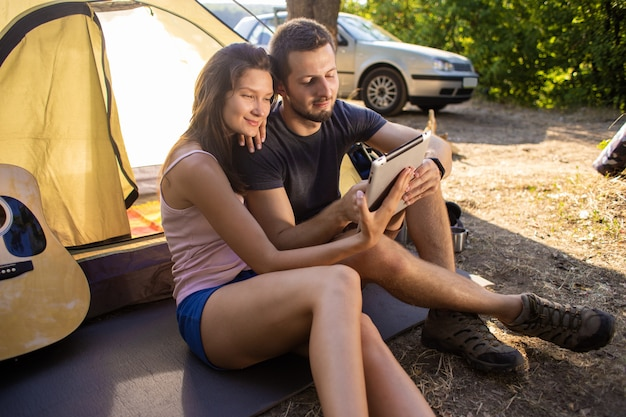 タブレットでテントの近くの男女。彼らは友達とビデオコミュニケーションについて話します Premium写真