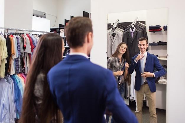 Девушка-продавец помогает подобрать клиента в галстуке-бутике мужской одежды Premium Фотографии
