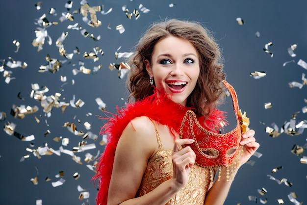 Восторженная женщина держит в руках красную карнавальную маску на праздничном фоне с мишурой Premium Фотографии