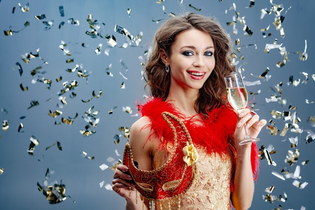 金色のドレスで陽気な女性は彼女の手に赤いカーニバルマスクとシャンパンの上げられたガラスを保持します Premium写真