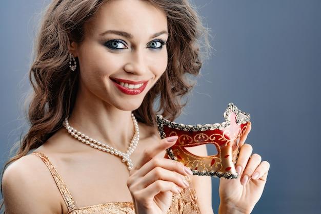 真珠のネックレス笑顔の若い女性は彼女の手のクローズアップでカーニバルマスクを保持します。 Premium写真