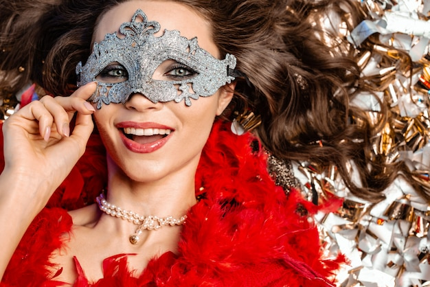 カーニバルマスクを着て黄金の見掛け倒しのクローズアップの間で床に横たわってうれしそうな若い女性 Premium写真