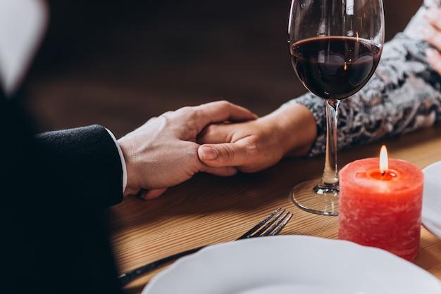 Среднего возраста влюбленная пара, держась за руки за столом в ресторане крупным планом Premium Фотографии