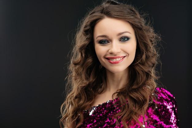 黒い壁を背景にポーズをとって幸せな若い女の肖像 Premium写真