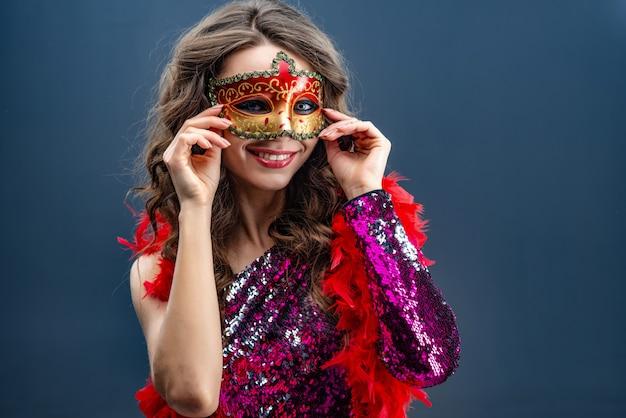 カーニバルマスクときらびやかなドレスを着た女性が笑っています。 Premium写真