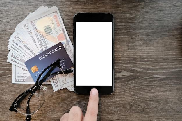 女性の手は、クレジットカードとコーヒーショップのテーブルの上のお金で空白のスマートフォンを保持します。 Premium写真