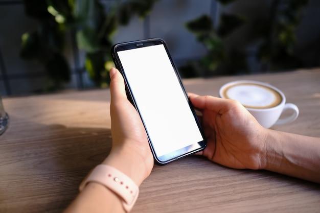 保持し、カフェで空白の画面を持つ黒い携帯電話を示す女性のモックアップ画像。 Premium写真