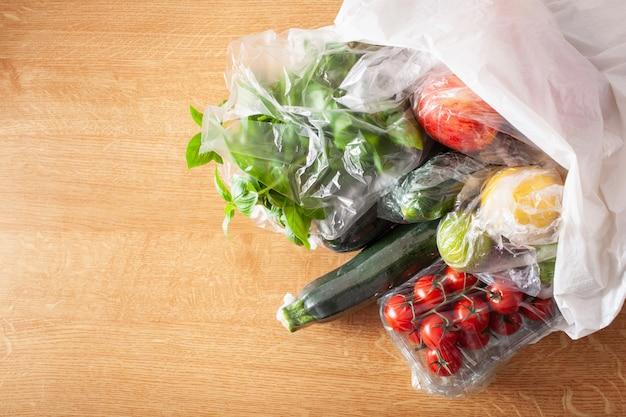 Одноразовый выпуск пластиковой упаковки. фрукты и овощи в полиэтиленовых пакетах Premium Фотографии